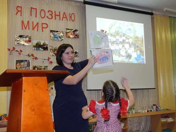 Воспитатель показывает папку с рисунками, девочка тянет руку