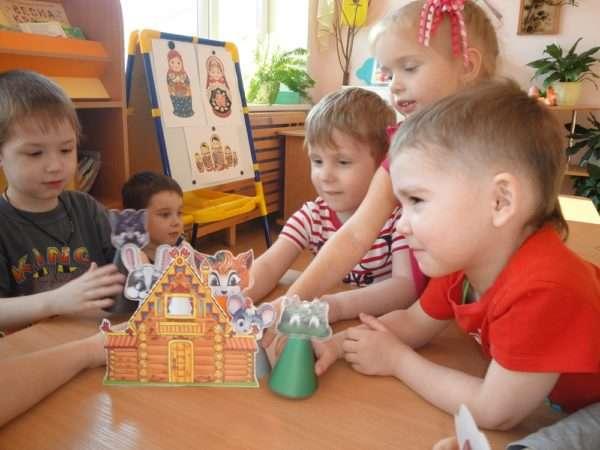 Три мальчика и девочка разыгрывают сказку «Теремок» на столе с картонными персонажами