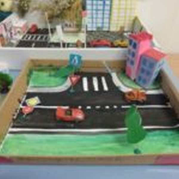 В коробке сделан макет проезжей части, на дороге стоит красная игрушечная машинка