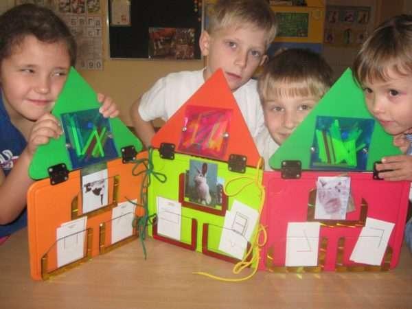 Четверо детей выглядывают из-за ярких дидактических домиков