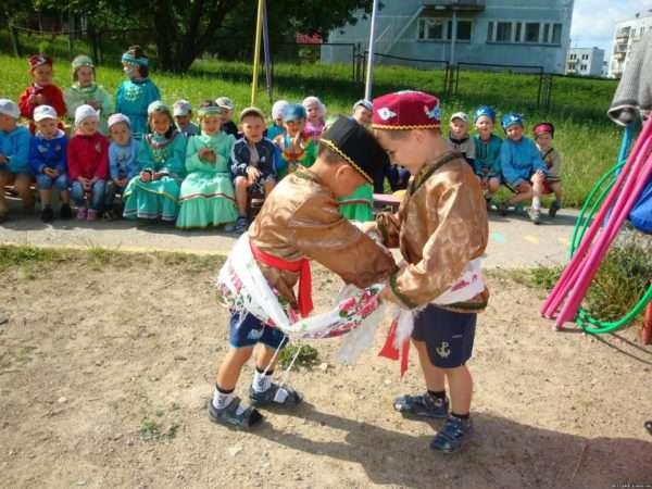 Два мальчика в национальных костюмах борются