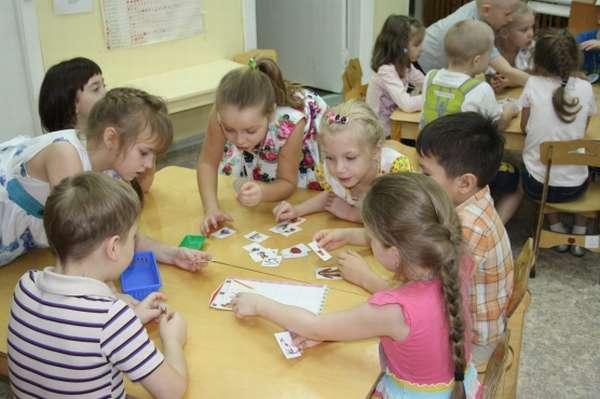 Дошкольники, сидя за столами, работают в командах