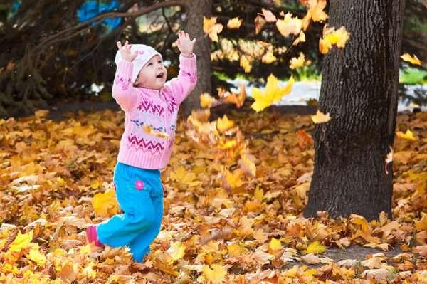 Девочка подбрасывает осенние листья в парке