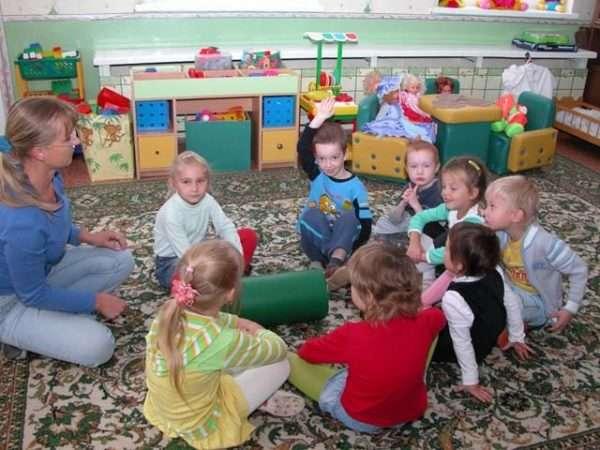 Воспитательница и дети сидят по кругу на коврике