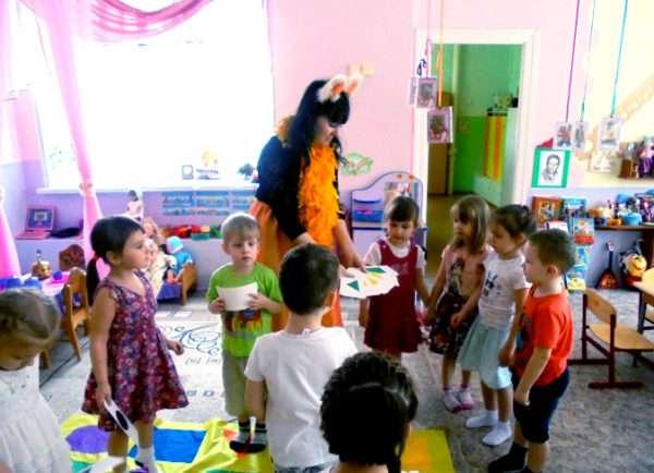Педгог в костюме лисички предлагает детям собрать геометрический ковёр