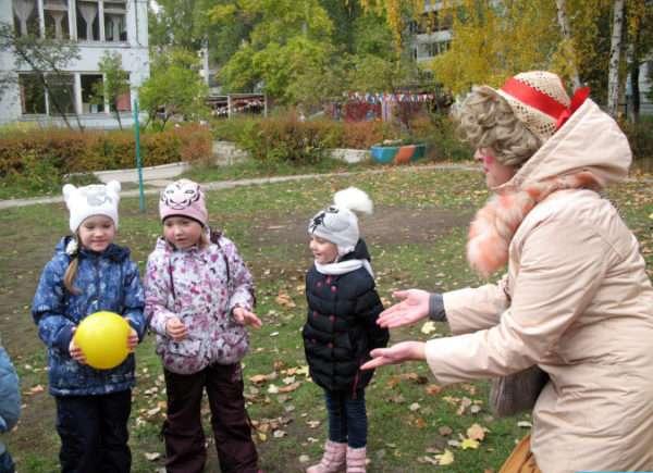 Дети и воспитатель играют с мячом на улице
