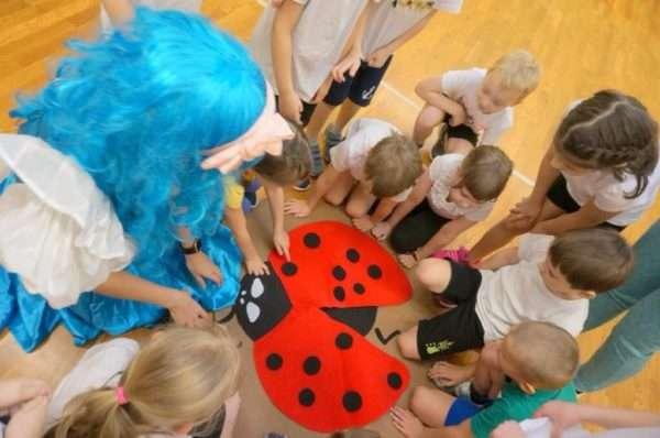 Дети и педагог в костюме Мальвины рассматривают бумажную божью коровку