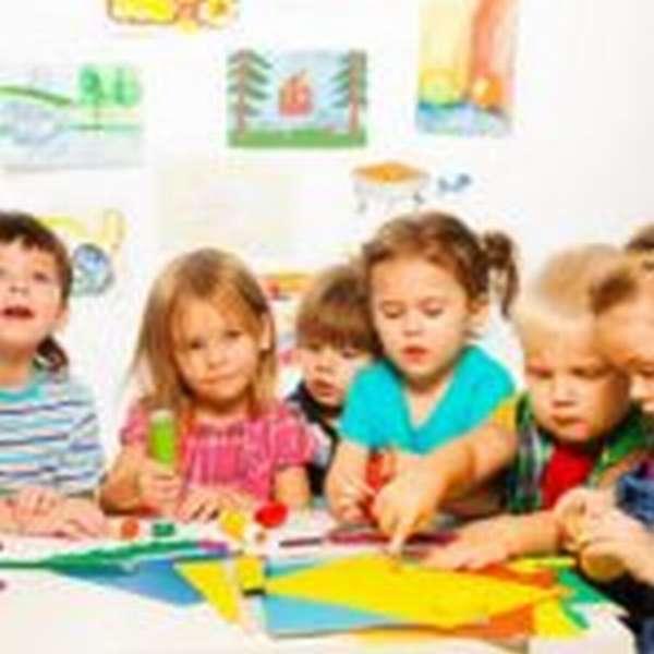 Дети за столом работают с цветной бумагой и клеем