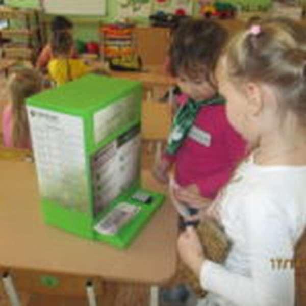 Две девочки стоят у самодельного банкомата