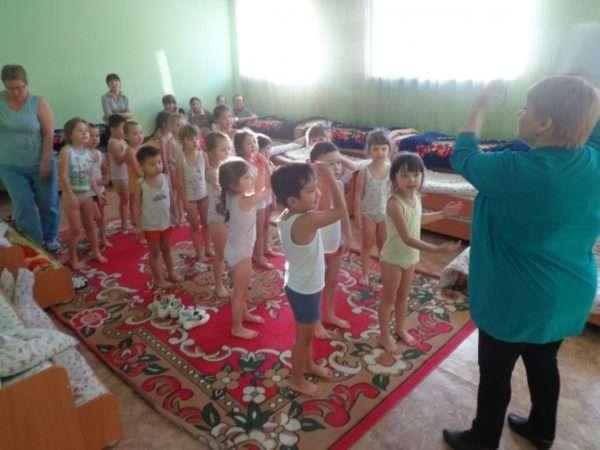 Воспитательница показывает движения, подняв руки вверх, дети стоя повторяют