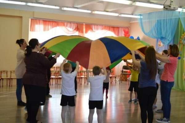 Дети и родители растягивают цветной шатёр