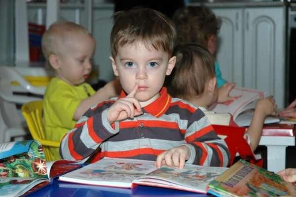 Мальчик сидит перед раскрытой книгой