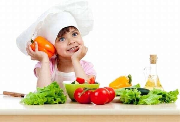 Ребёнок в колпаке повара сидит с перцем в руках