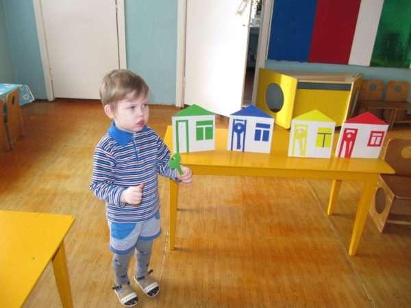 Мальчик держит в руке ключ из зелёного картона, рядом на столе стоят разноцветные домики