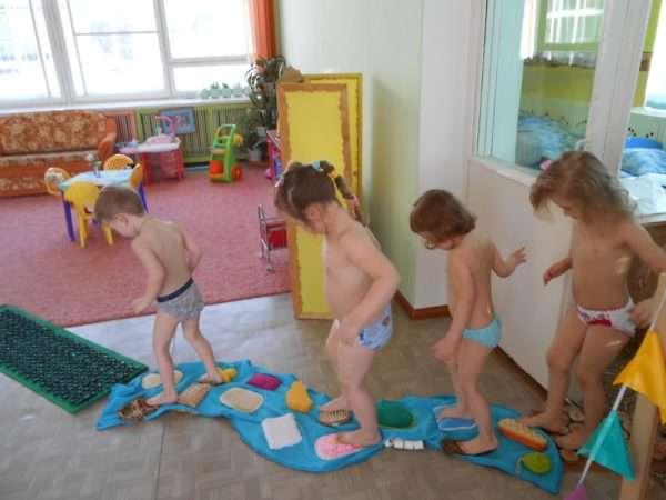 Дети ходят по сенсорным коврикам