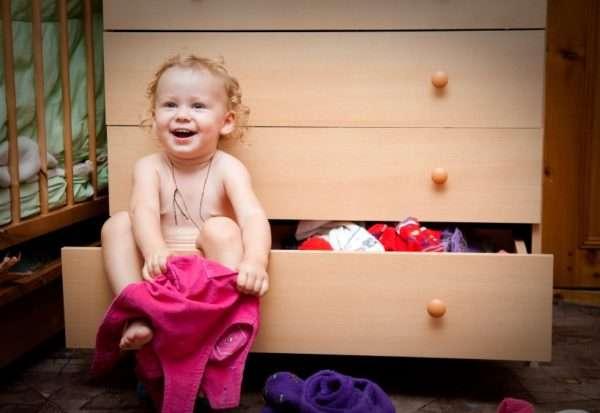 Девочка сидит в открытом ящике комода и одевается