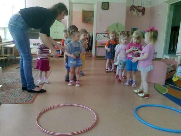 Дети стоят в колоннах перед лежащими на полу обручами, педагог объясняет задание