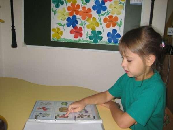 Девочка, сидя за столом, рассматривает картинки