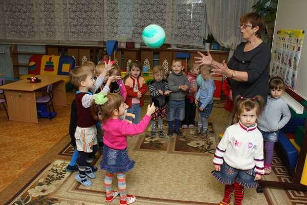 Воспитатель бросает детям мяч