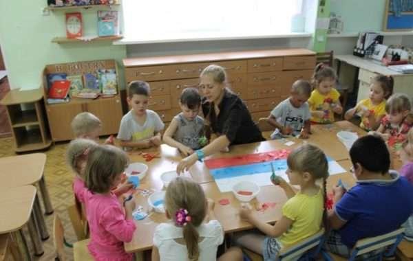 Дети за столом делают аппликацию российского флага