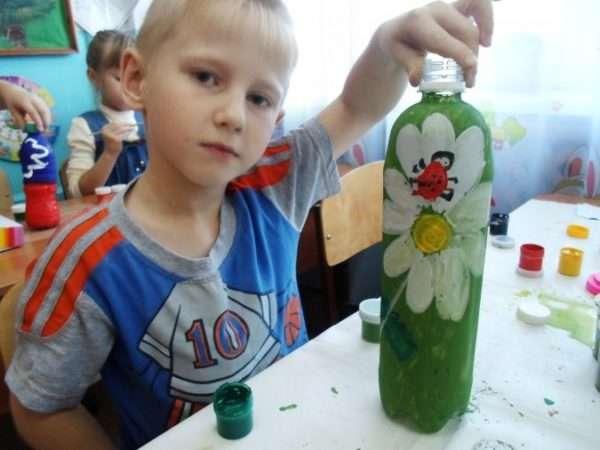Мальчик держит раскрашенную бутылку