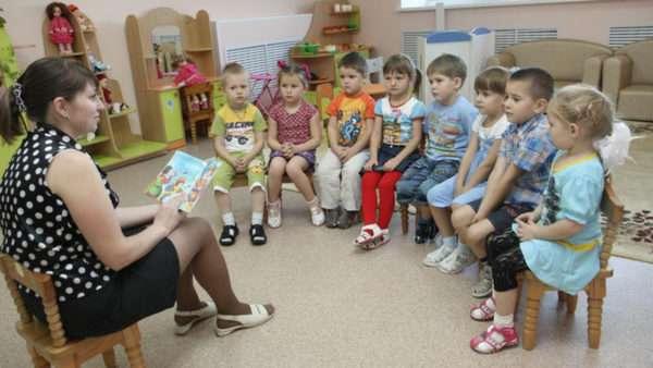 Воспитательница читает книжку детям, сидящим полукругом