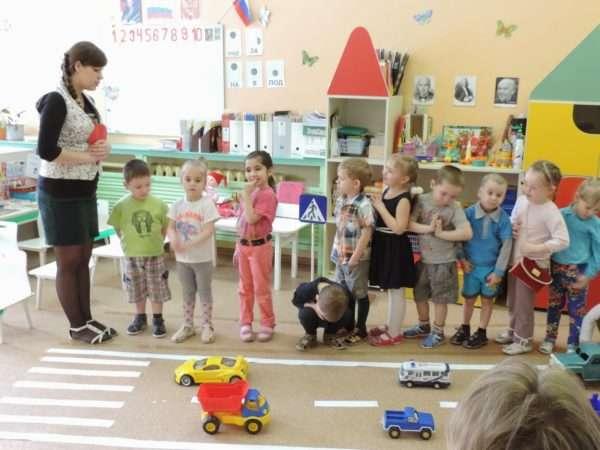 Воспитательница что-то говорит детям, стоящим цепочкой перед имитацией пешеходного перехода