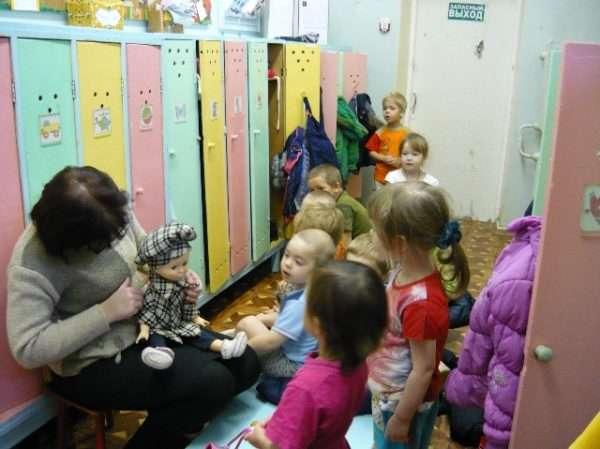 Дети собираются на прогулку, воспитатель держит в руках куклу