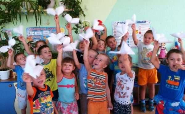 Дети с бумажными фигурками голубей в руках