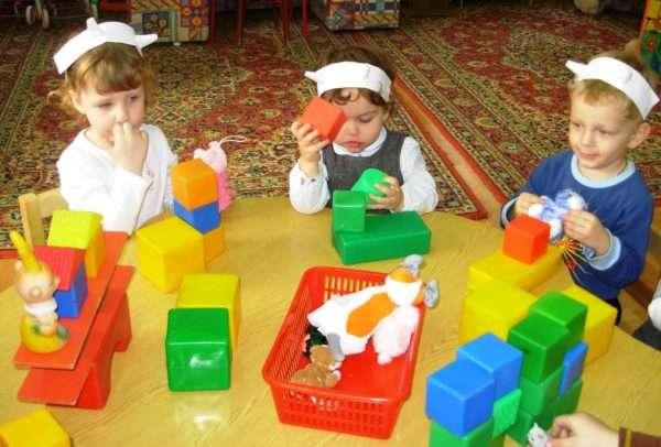 Трое детей в шапочках с рожками строят домики из кубиков