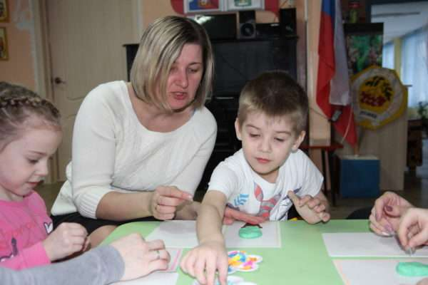 Воспитатель подсказывает мальчику, как выполнить аппликацию