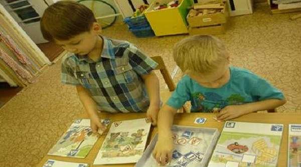 Два мальчика раскладывают знаки на карточки