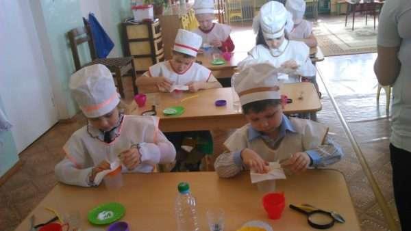 Дети в белых шапочках и фартуках проводят опыты с водой и бумагой