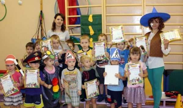 Дети с грамотами с бумажными светофорами на голове и дорожными знаками в руках, воспитательница в синей сомбреро