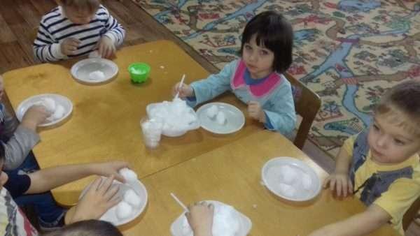 Дошкольники, сидя за столами, проводят опыты со снегом