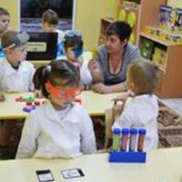 Дети и воспитатель, сидя за партами, проводят эксперимент