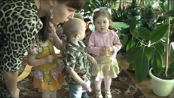 Дети с воспитательницей рассматривают цветы в горшках на полу