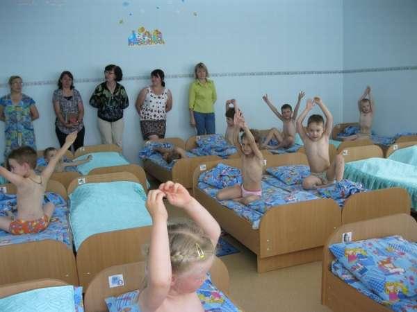 Дети в кроватках сидят, подняв руки вверх