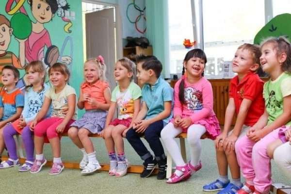 Дети сидят на скамейке в группе