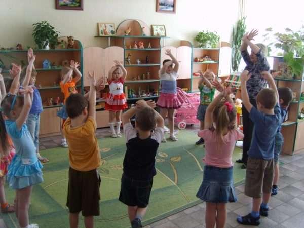 Дети и педагог стоят в кругу с поднятыми вверх руками