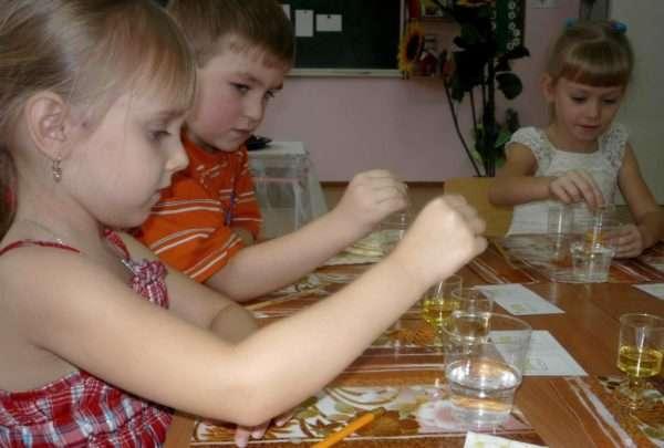 Трое детей, сидя за столом, проводят эксперимент с водой и маслом