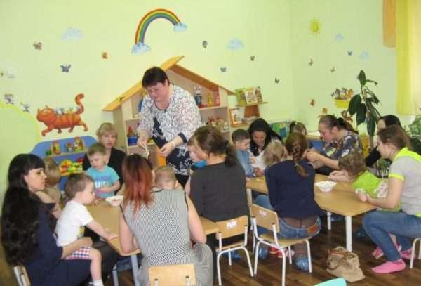 Родители сидят с детьми за столами в группе