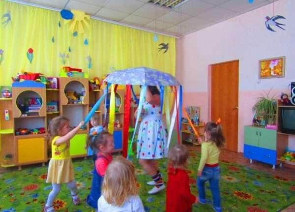 Воспитательница держит зонт, к спицам которого привязаны разноцветные ленты, за них держатся дети