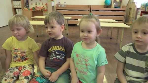 Четверо детей сидят на стульях