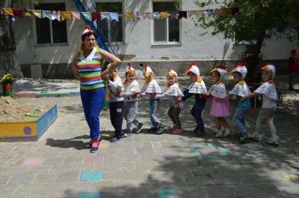 Дети в шапочках цыплят идут за воспитательницей в шапочке курицы