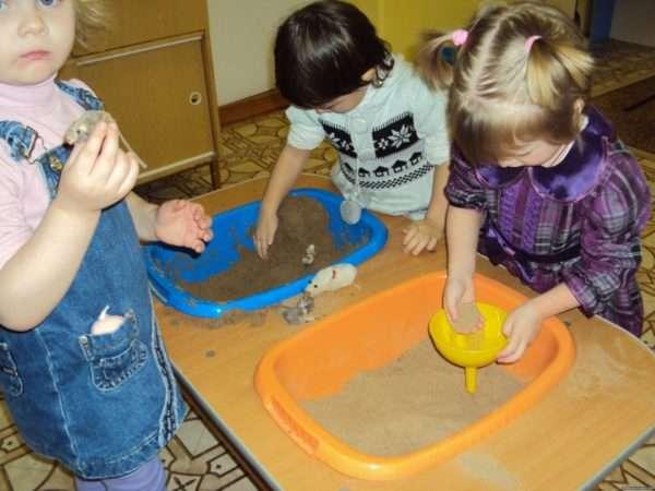 Дети изучают свойства сухого и сырого песка в центре экспериментирования