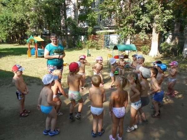 Дети в трусиках выполняют упражнения на улице