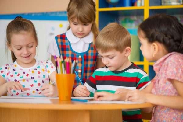 Четверо детей рисуют цветными карандашами