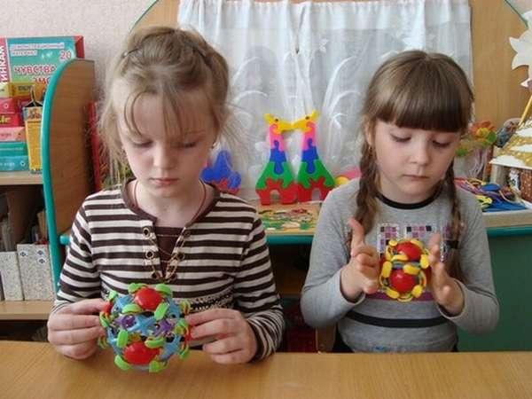 Две девочки крутят игрушки с фигурками
