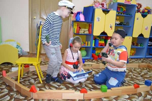 Два мальчика и девочка играют в плавание на корабле